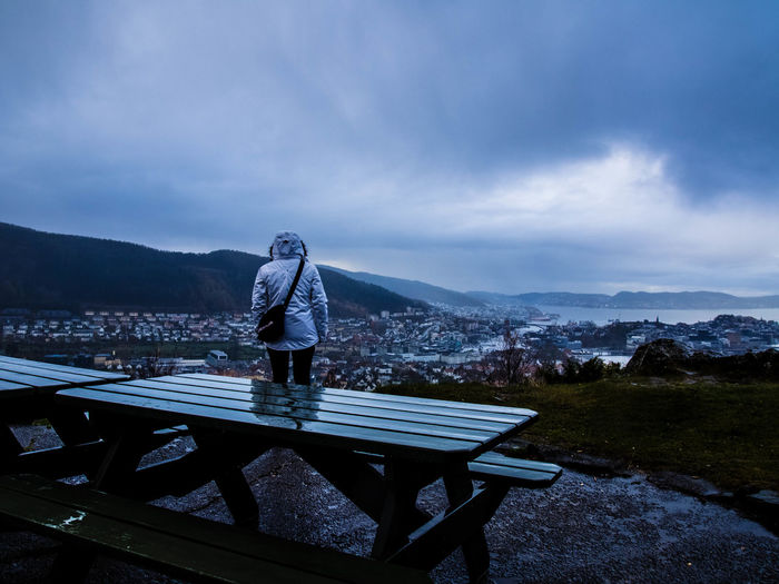 Person standing on bench against mountains