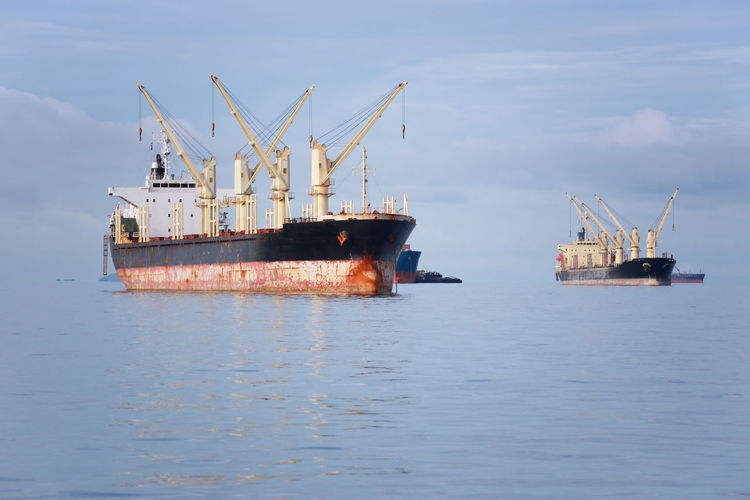 cargo ship in the sea,daytime sky. Nautical Vessel Sea Water Ship Transportation Industry Freight Transportation Waterfront No People Shipping  Crane - Construction Machinery Mode Of Transportation Business Offshore Platform Container Ship Sky Day Oil Industry Nature Outdoors