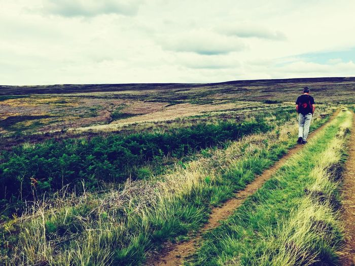 Rear View Of Man Walking On Field Against Cloudy Sky At North York Moors