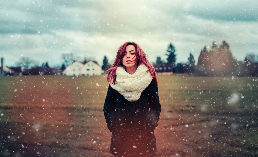 Portrait of young woman standing on field against cloudy sky during snowfall