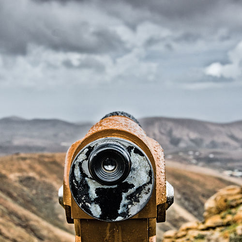 Close-up of weathered coin-operated binoculars against sky