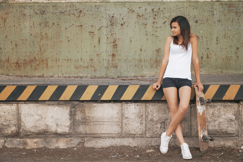 Woman standing with skateboard against wall