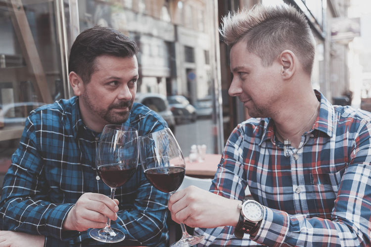 Gay couple toasting red wine while sitting at outdoor restaurant