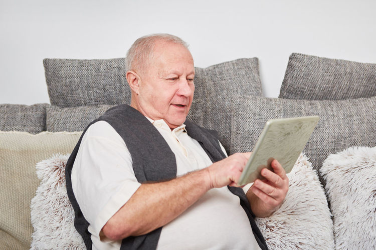 Man Using Digital Tablet While Sitting On Sofa At Home