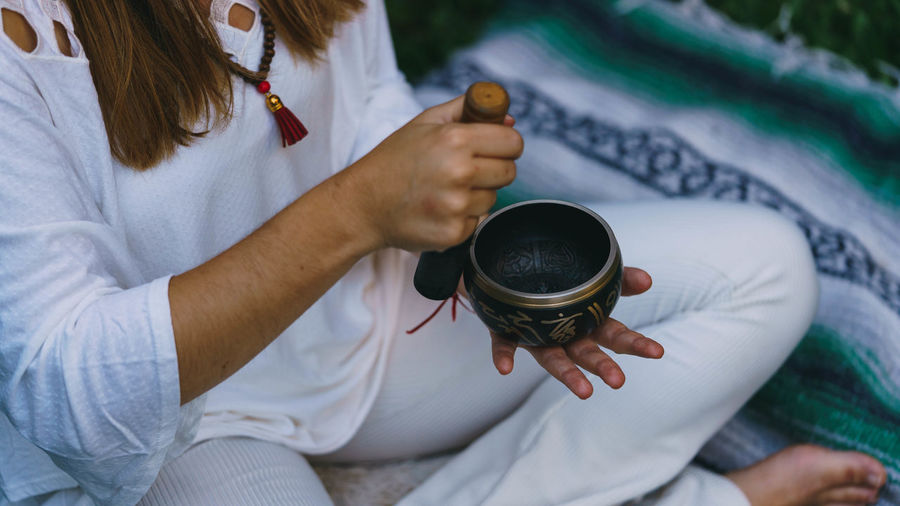 High angle view of woman holding tibetan singing bowl