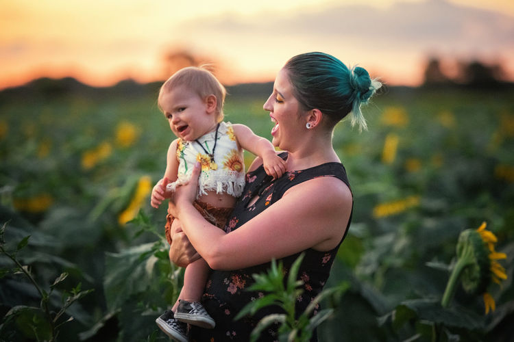Happy mother with daughter standing in sunflower farm