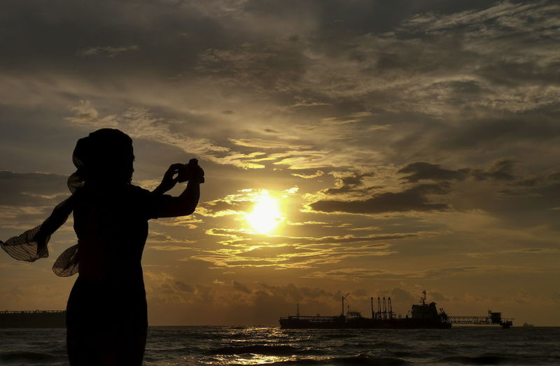 Silhouette. A woman on the beach by taking pictures of beautiful scenery on January 02, 2019 Sky Sunset Cloud - Sky Water Sea Standing Real People Photographing Photography Themes Beauty In Nature Silhouette Nautical Vessel One Person Nature Leisure Activity Technology Orange Color Activity Camera - Photographic Equipment Wireless Technology Outdoors Photographer