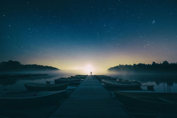 Distant View Of Person Standing On Jetty By Boats Moored On Lake Against Starry Sky
