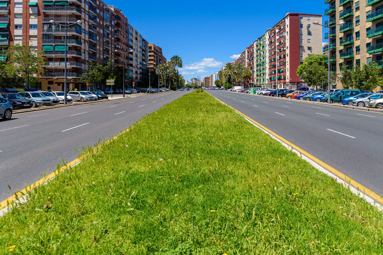 Surface level of road amidst buildings against sky