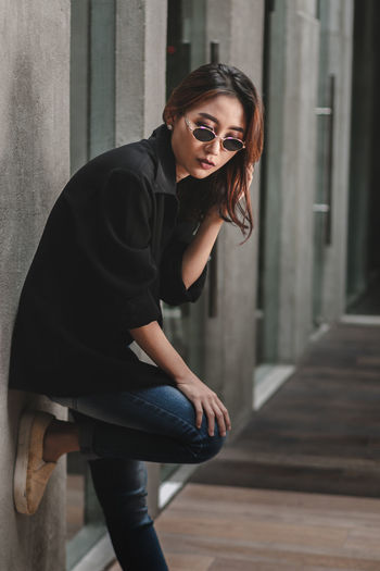 Portrait of woman standing against wall