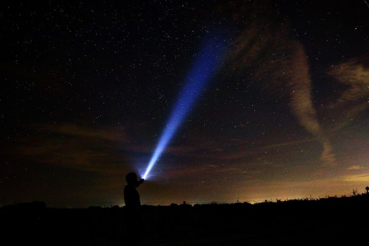 Silhouette Person With Laser Light Against Sky At Night