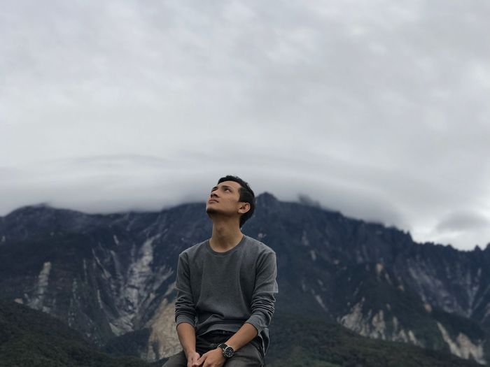 Young man sitting against mountains