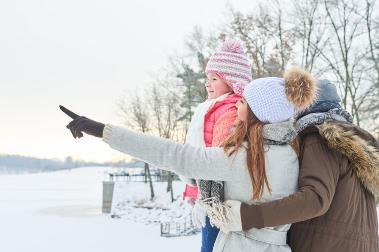 Woman pointing with family against sky during winter
