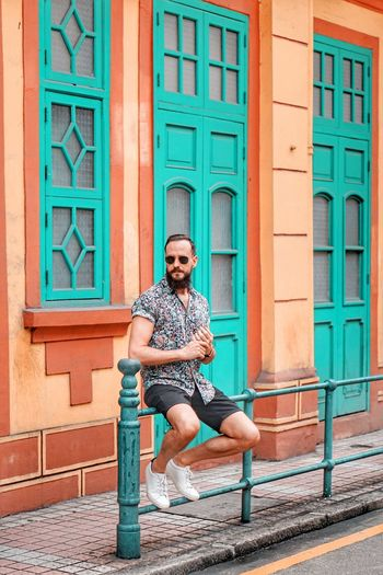 Architecture One Person Full Length Young Men Young Adult Fashion Lifestyles Sunglasses Front View City Adult Building Exterior Glasses Built Structure Leisure Activity Real People Sitting Casual Clothing Beard Outdoors