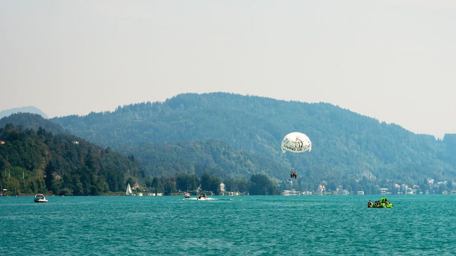 WORTHERSEE, AUSTRIA - AUGUST 08, 2018: View from the boat to the lake and coastline. Local residents and tourists swim, driven by motorboats and use other forms of water recreation. Nature Day Outdoors Austria Carinthia Carinthian Lakes Tourist Tourists Lake Wörthersee Recreation  Leisure Landscape Water Sea Boats Motorboat Speedboats Summer People Holidays Fun Travel Beach Resort Lifestyle Sunny Rest Joy Waves Europe Alps Alpine Alpine Lake Nautical Vessel Waterfront Sky Transportation Mountain Mode Of Transportation Scenics - Nature Clear Sky Copy Space Beauty In Nature Travel Destinations Group Of People Incidental People Turquoise Colored