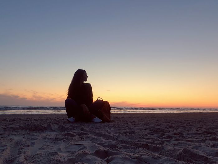 Woman sitting at beach against sky during sunset
