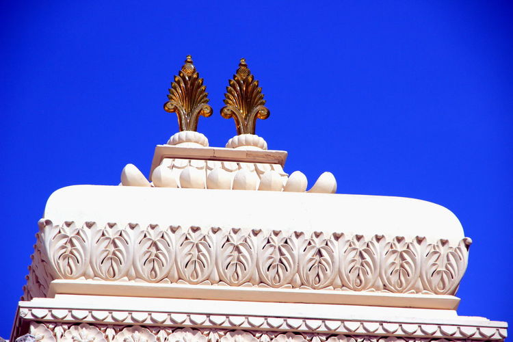 Low angle view of temple against building against clear blue sky