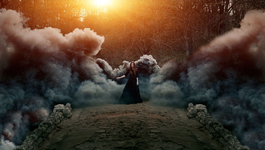 Digital composite image of woman wearing dress while standing in forest amidst smoke