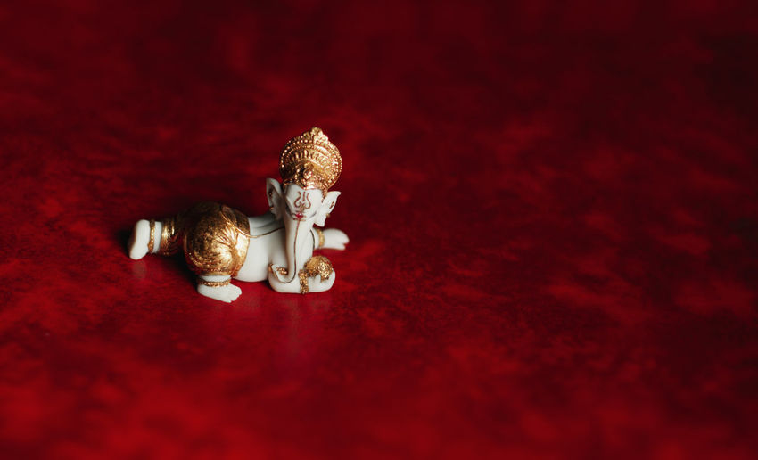 Close-up of ganesh statue on red background