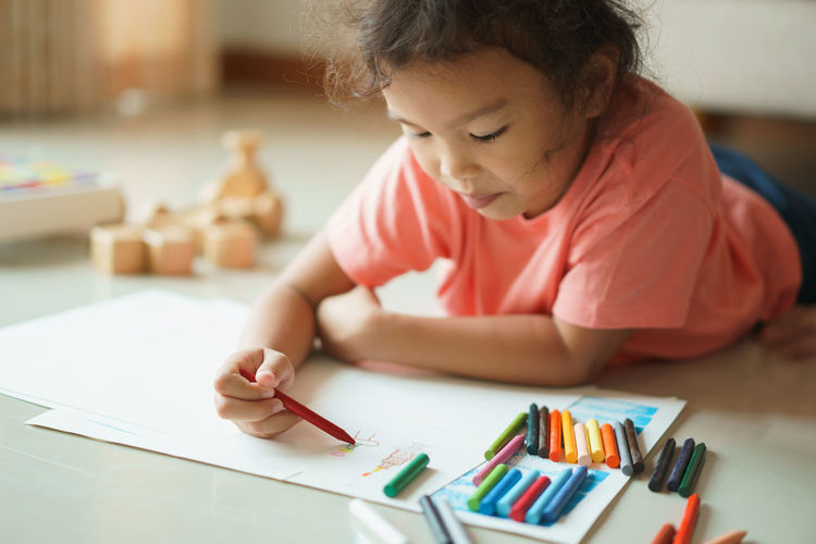 Girl coloring on paper while lying at home