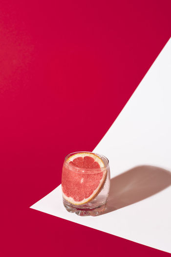 Close-up of drink on table against red background