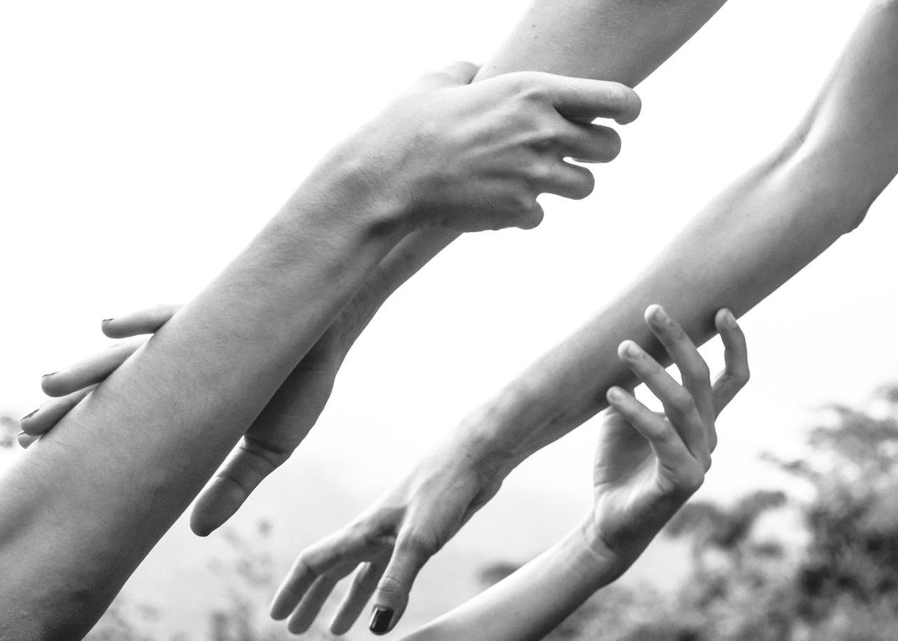 Low angle view of couple holding hands against sky
