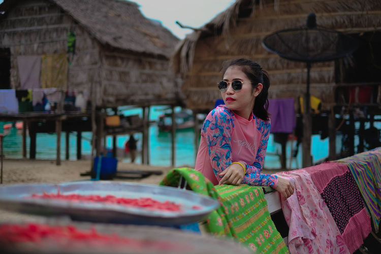 Woman in sunglasses standing by hut