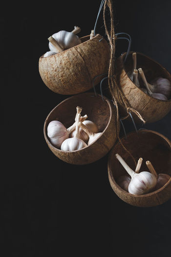 High Angle View Of Garlic Bulbs Hanging Against Black Background