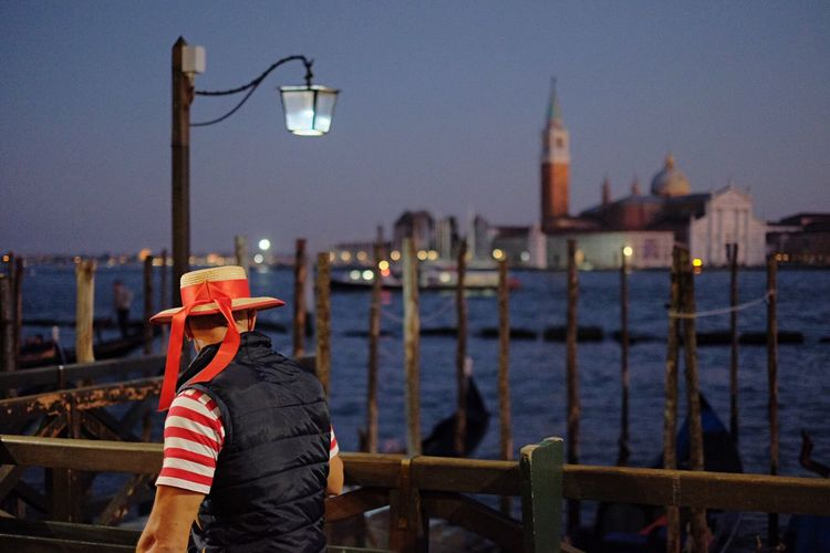 Man in hat against grand canal and church of san giorgio maggiore in city at dusk