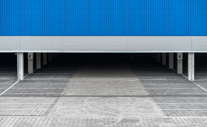 Empty parking area amidst building in city