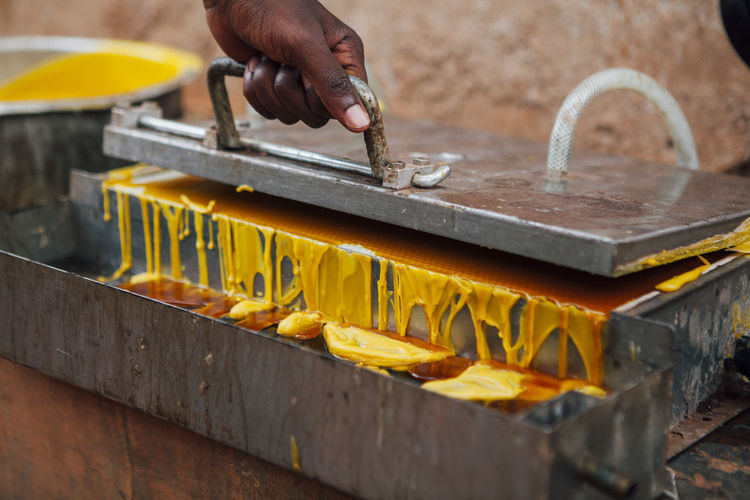 Cropped image of person opening metal container with wax on field