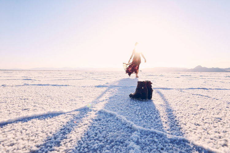 Rear View Of Woman Walking At Bonneville Salt Flats On Sunny Day