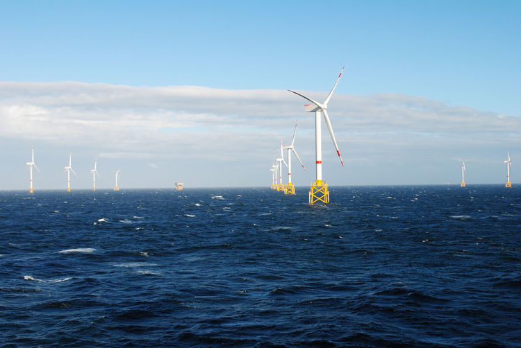 Wind turbines in sea against sky