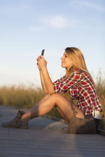Side view of young woman using mobile phone against sky