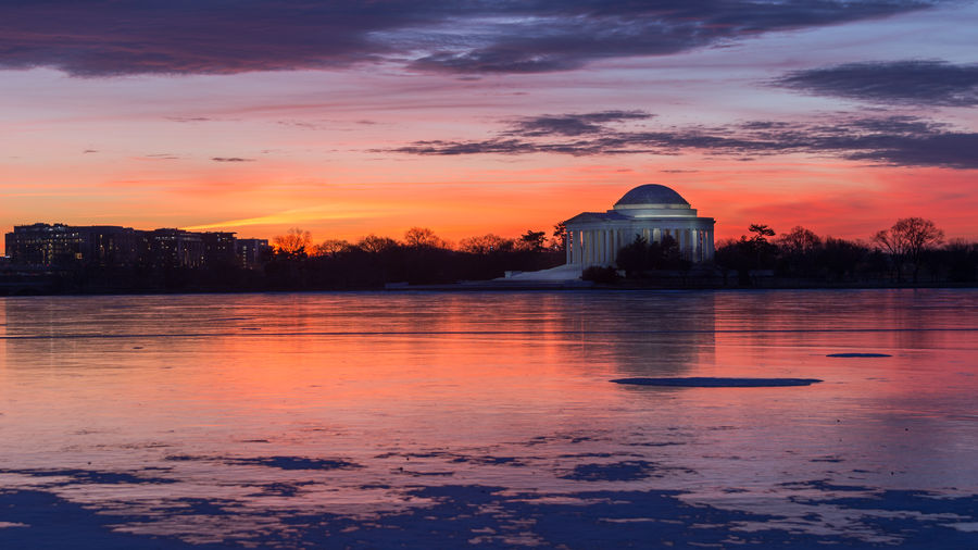 Red and orange colors are cast at sunrise over a frozen Tidal Basin and Jefferson Memorial in Washington, D.C. Frozen Ice Tidal Basin Tranquility Washington, D. C. Winter Architecture Building Exterior Built Structure Cold Cold Temperature Day Dome Jefferson Memorial Nature No People Outdoors Reflection Sky Sunrise Sunset Tranquil Scene Travel Destinations Water Waterfront