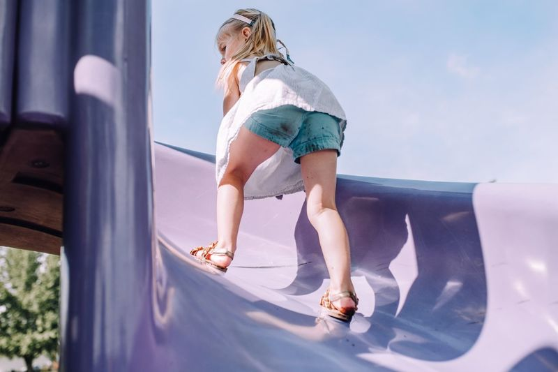 Full length of girl playing on slide against sky