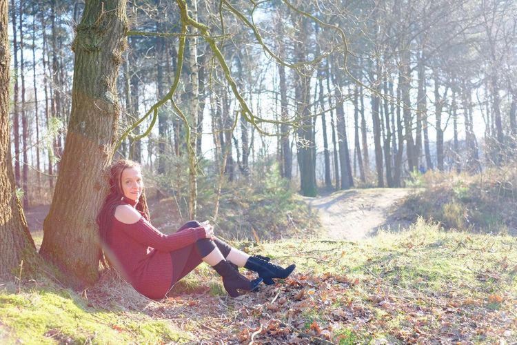 Beautiful young woman in the woods sitting against a tree Portrait Tree Plant One Person Leisure Activity Lifestyles Full Length Land Nature Forest Women Sitting Adult Casual Clothing Sunlight Relaxation Real People Tranquility Beauty In Nature WoodLand Outdoors