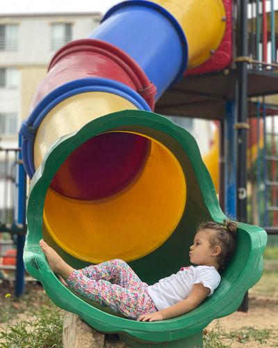 Full length of cute girl sitting on slide at playground
