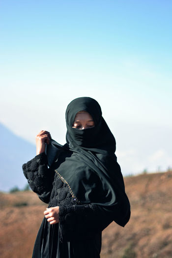 natural and muslim clothing in the mountain Modern Black Color Clothing Day Expression Focus On Foreground Front View Headscarf Hijab Hood Hood - Clothing Lifestyles Mountain Muslim Nature One Person Outdoors Portrait Real People Sky Three Quarter Length Traditional Traditional Clothing Veil Women