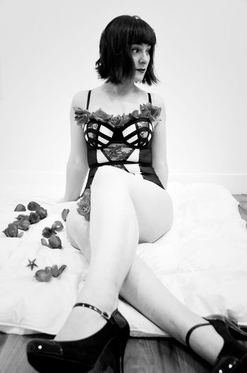 Young woman wearing lingerie sitting on bed by artificial flowers at home