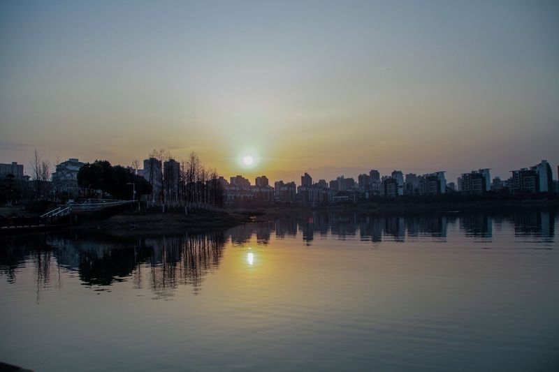 Scenic View Of River By Silhouette Buildings Against Sky During Sunset