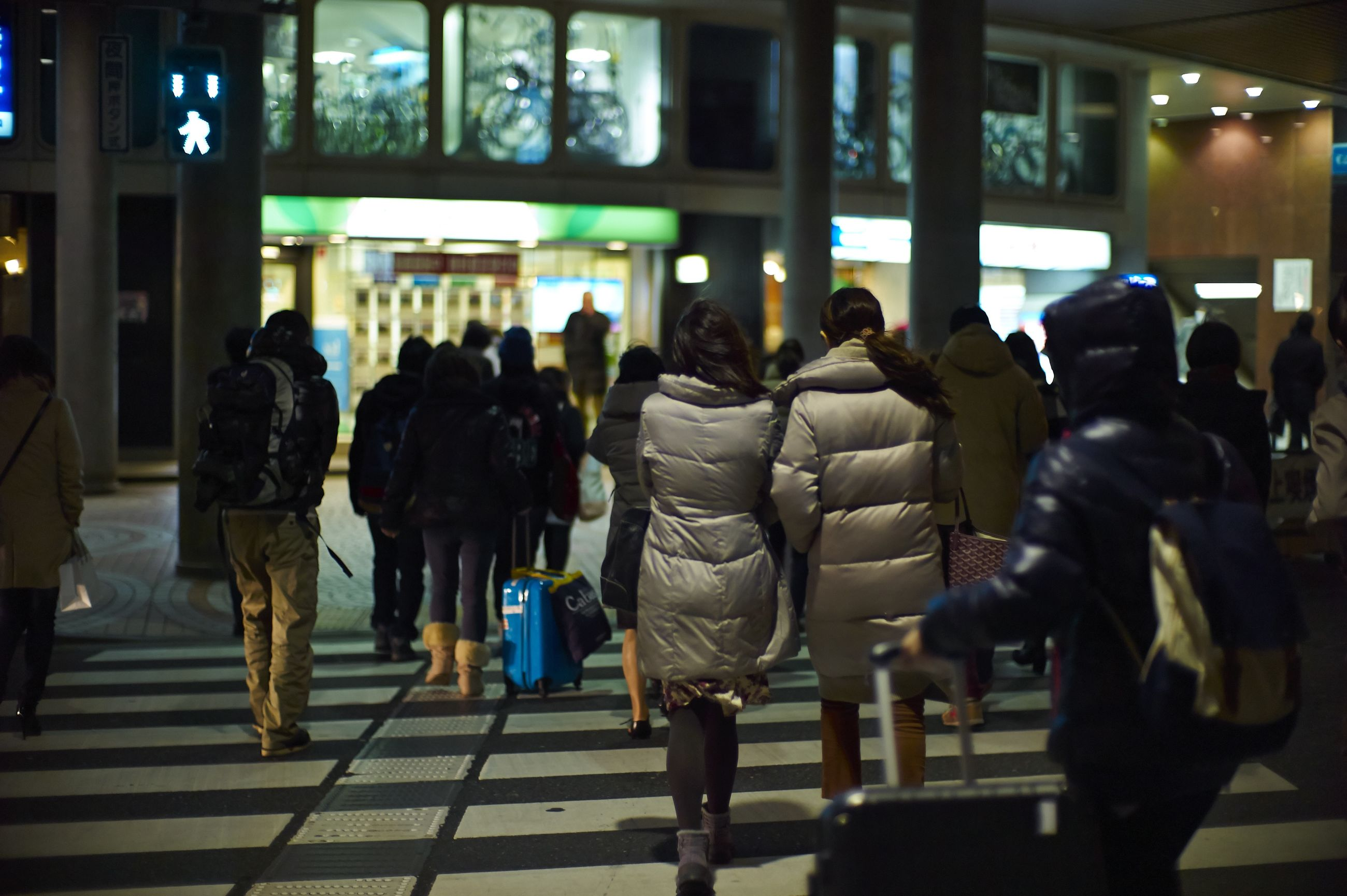 indoors, men, person, lifestyles, large group of people, illuminated, walking, standing, leisure activity, night, built structure, railroad station, city life, medium group of people, architecture, group of people, rear view, city, public transportation