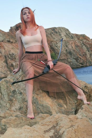Full Length Of Young Woman Holding Bow And Arrow While Sitting On Rock
