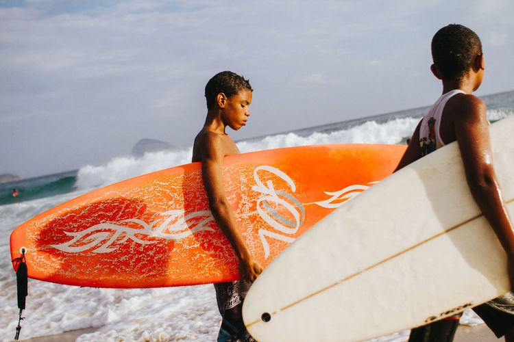 Surfer kids in Rio de Janeiro, Brazil The Art Of Street Photography Young Women Sitting Togetherness Sea Curly Hair Beach Friendship Water Adventure Sky Surfer Surfboard Surfing Surf Water Sport
