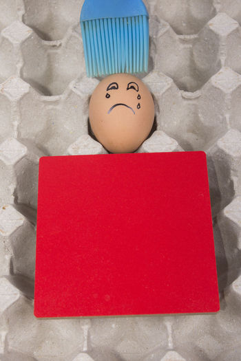 Cartoon face expression at egg and red board with finger also plastic brush Angry; Anthropomorphic Face Anthropomorphic Smiley Face Blue Brush; Blue Plastic Brush; Brush; Close-up Confuse; Excited; Expression; Human Representation Indoors  Joke; No People Plastic; Sad; Scare; Shy; Sick