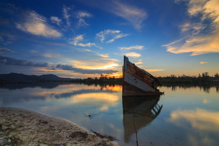 Abandon Old wreck on the shore , Borneo , Old fishing boat with the reflection on sunset moment Beauty In Nature Cloud - Sky Lake Mode Of Transportation Moored Nature Nautical Vessel No People Non-urban Scene Outdoors Reflection Rowboat Scenics - Nature Sinking Sky Sunset Tranquil Scene Tranquility Transportation Water Waterfront