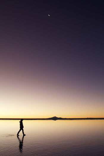 Silhouette person walking on wet shore against clear purple sky
