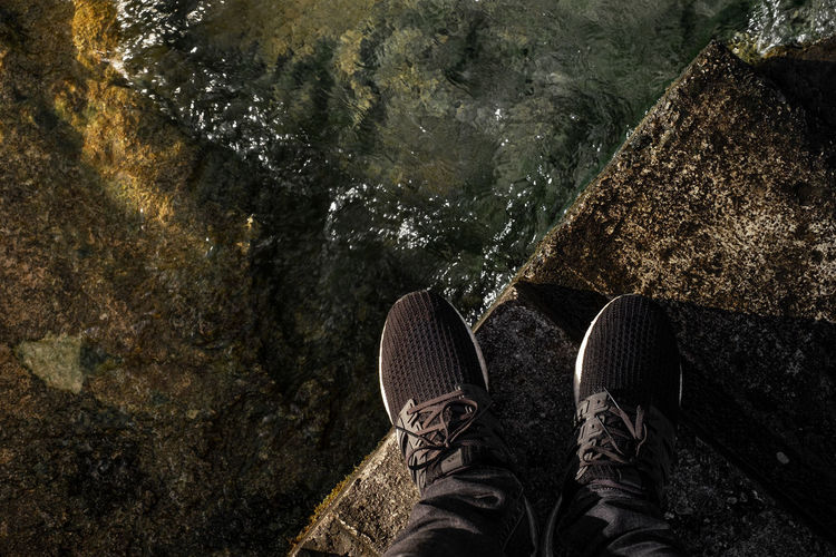 Low section of person standing on retaining wall by lake