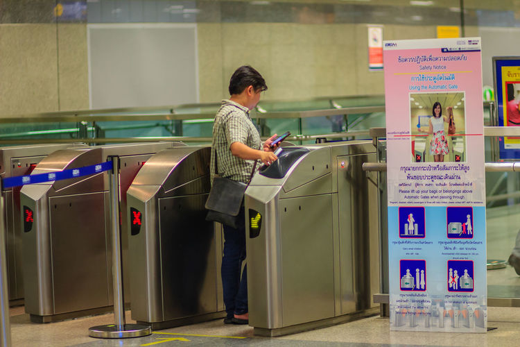 Bangkok, Thailand - April 23, 2017: Unidentified passenger use coin ticket touch with the automatic access barrier to enter to Chatuchak MRT (Metropolitan Rapid Transit) subway station. Adult Automatic Access Barrier Casual Clothing Coin Ticket Communication Full Length Holding Indoors  Lifestyles Men Mid Adult Occupation One Person Real People Side View Standing Subway Station Subway Station Sign Subway Station View Technology Text Western Script Working