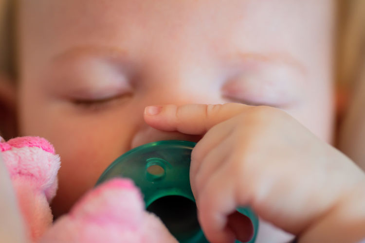 Close-up of baby girl sleeping with pacifier